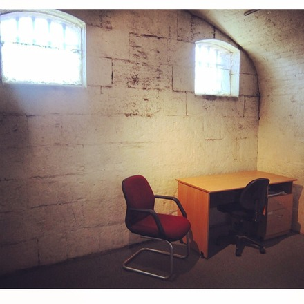 A photo of Studio 7 at Old Melbourne Gaol, featuring a curved, stone roof, a small empty desk and two chairs
