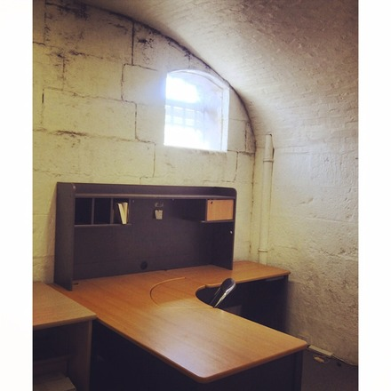 A photo of Studio 5 at Old Melbourne Gaol, featuring a single chair, a desk and one small, high window