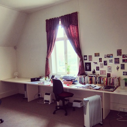 A photo of Studio 4 at Glenfern, with  with a long desk beneath a red-curtained window. The desk is covered in books, tea cups and writing research. The wall is covered in images.