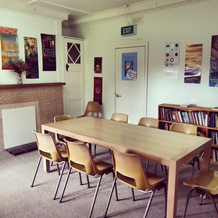Photo of the Glenfern meeting room, featuring a large communal table in front of bookcases