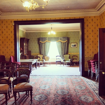 Photo of the Grand Room at Glenfern, featuring antique furniture, patterned carpets and sweeping curtains